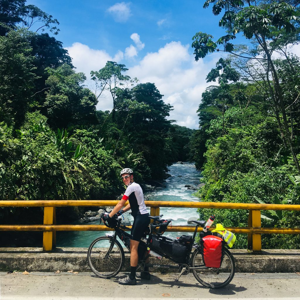 man with tandem bike overlooking a river in South America