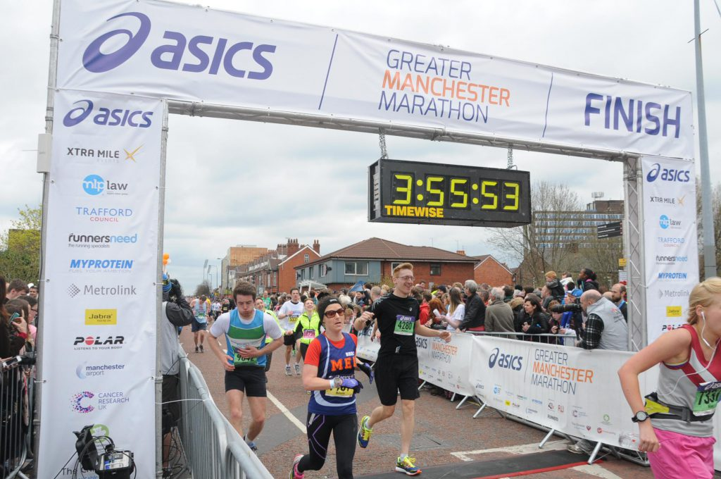 man crossing finishing line of a marathon event