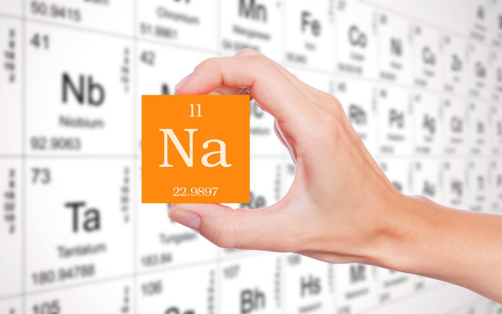 Image of a hand holding a cube showing the chemical symbol for sodium
